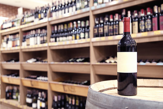 Bottle of red wine on a barrel in a wine store