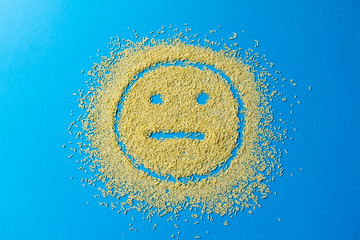 confectionery sprinkles shape of the sad emoji smile. yellow sugar grains on a blue background.