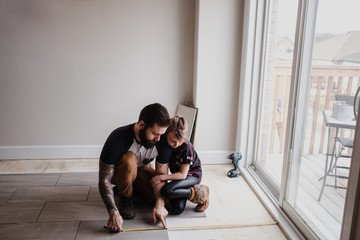 Girl helping father install floor tiles