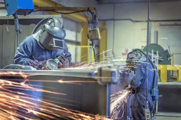 Workers using grinders in engineering factory