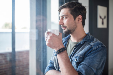 Young man drinking coffee while looking out of  office window