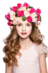 Beautiful baby girl portrait with flowers on head and curly hair.