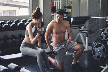 Fitness man and asia woman doing exercise in gym