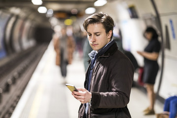 UK, London, businessman waiting at underground station using cell phone