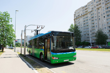 Electric bus at a stop is charged by pantograph