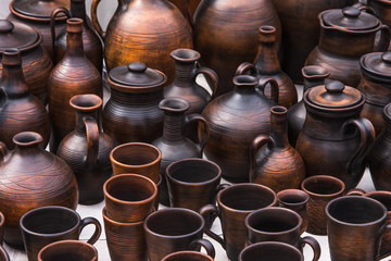 Traditional rural cups, jugs and plates of clay on the counter of a street shop