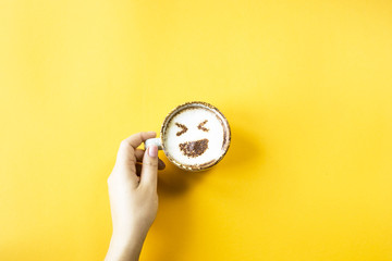A female hand holds a cup of coffee on which is drawn emoji laughter. Emotions in social networks concept. Top view, flat lay