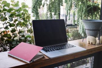 Notebook near laptop in garden