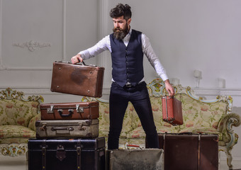 Macho elegant on thoughtful face standing near pile of vintage suitcase. Man, traveller with beard and mustache packing luggage before trip, luxury interior background. Luggage and travelling concept.