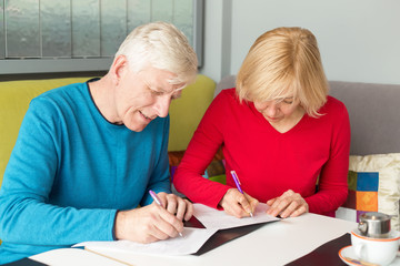Adult couple husband and wife fill out the documents, insurance policy. Man and woman, couple pensioner aged.