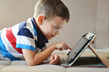 Little cute boy in a green T-shirt playing games on a tablet and watching cartoons. Toddler with tablet.