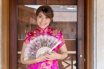 Portrait beautiful young woman wear cheongsam deep pink dress holding a fan looking at camera. Festivities and Celebration concept