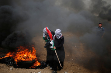 Female Palestinian demonstrators walk past a burning tire during a protest demanding the right to return to their homeland, at the Israel-Gaza border, east of Gaza City
