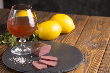 Piece of meat  with lemon and cognac on wooden background