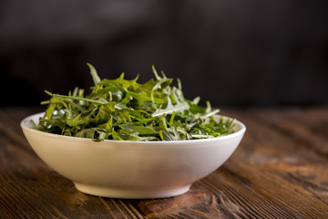 arugula in white bowl on wooden background