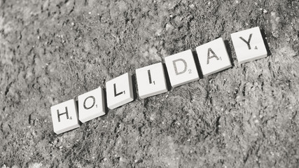 Wooden puzzle of Holiday sign on beach background summer