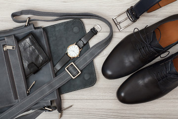 Leather shoulder bag for men with wallet and wristwatch on it, belt for men and pairs of black leather men's shoes