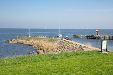 Breakwater with sailing ship near harbor of Medemblik, The Netherlands