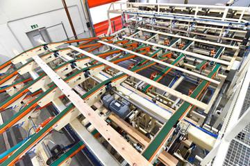 Produktion von Holzbrettern im modernen Sägewerk - moderne Industriemaschine mit Fliessbandfertigung  // Production of wooden boards in a modern sawmill - industrial machine