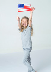 Patriotic girl with the flag of United States of America on a gray background. Blond girl 6 years old in a shirt.