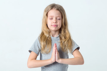 Little girl with her eyes closed folded her hands in prayer or meditation.