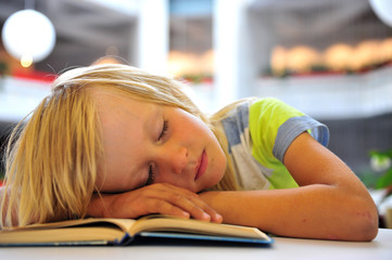 Little boy dreaming with a book