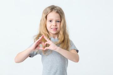 Little girl shows hands a heart sign standing on a light background.
