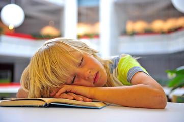 Cute little boy sleeping in library