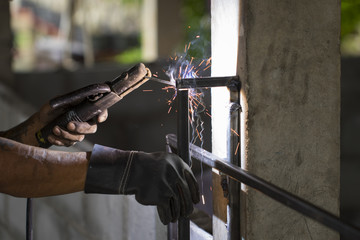 Image of worker welding metal and producing smoke and sparks.