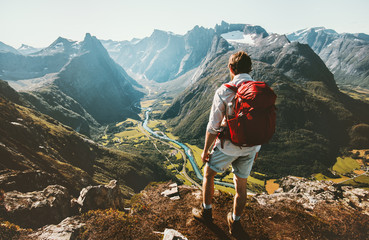Hiking alone in Norway mountains Man with red backpack enjoying landscape on cliff solo traveling healthy lifestyle concept active summer vacations Wall mural