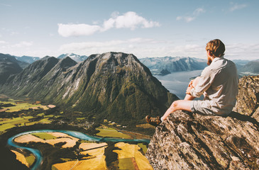 Man sitting on cliff edge relaxing with aerial mountains landscape Travel lifestyle adventure vacations in Norway traveler thinking alone