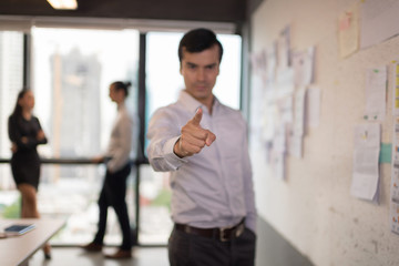Selective focus at finger. Confident businessman in office with blur business people working background.Work space concept.
