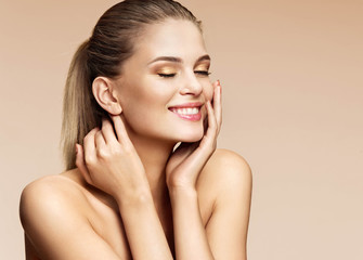 Happy smiling blonde girl touching her clean skin face. Photo of attractive girl with beautiful makeup on beige background. Youth and skin care concept
