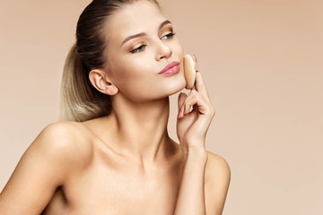 Attractive girl applying powder on her face with cosmetic application. Photo of young girl on beige background. Youth and skin care concept
