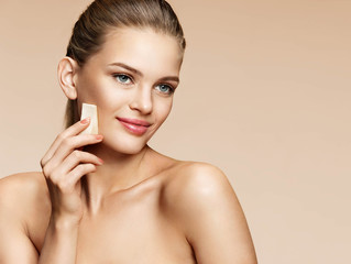 Smiling young girl applying foundation on her face using makeup sponge. Photo of gorgeous girl on beige background. Perfect makeup