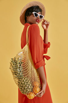 Studio portrait of beautiful young black woman with short brown hair, red lips, dressed in orange red dress, white sunglasses, hat, with fruits in net bag. Yellow background