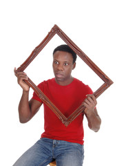 Surprised African man holding up a window frame