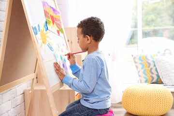 Little African-American boy drawing indoors