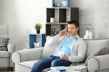 Young man talking by mobile phone on sofa at home