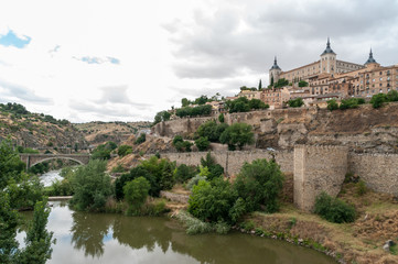 Landscape of Toledo, Spain, with Alcazar, the river Tajo and a dramatic sky with clouds.