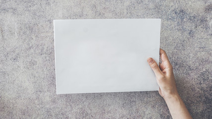 Hand holding blank white paper