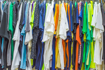 Multicolored old clothes on the hangers in the store