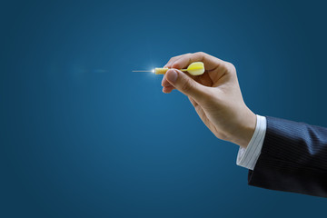 Hand of a businessman to aim with a dart .