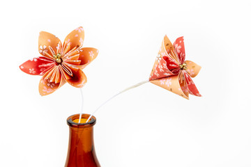Two orange origami flowers in dark glass bottle on white background.