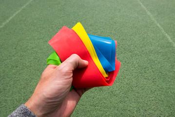 Hand mit Gummibändern auf Sportplatz