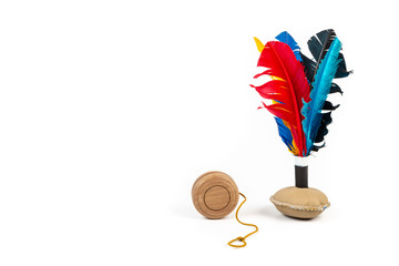 A wooden yo-yo and a handmade shuttlecock toy with colourful feathers on white background.