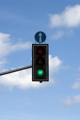 Green signal of street light, straight direction arrow against blue sky