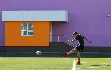 A boy kicks a ball on a football pitch in Saransk