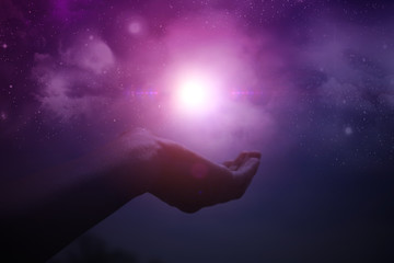 Hands holding light with night sky and stars in the background
