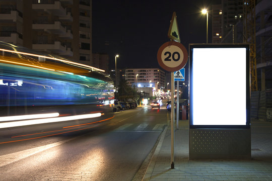 Advertising billboard near the road. White billboard. Blurred motion. Mock up.